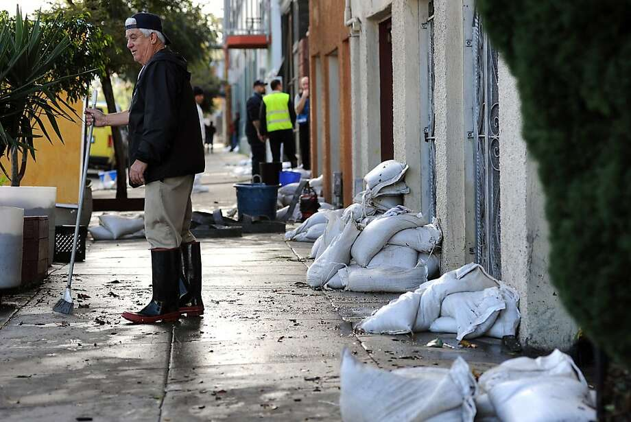 Building manager Sam Piccazo stands on Folsom Street in S.F. where, despite sandbags, buildings were flooded after last week's storm. Photo: Michael Short, Special To The Chronicle