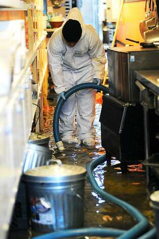 Workers from Servicemaster Restoration Services pump out standing water in the kitchen area of Stable Cafe on Folsom St.  Business on the 2100 block of Folsom St. in San Francisco were flooded this morning by water that backed up through the sewage lines.  Sunday December 2nd, 2012. Photo: Michael Short, Special To The Chronicle