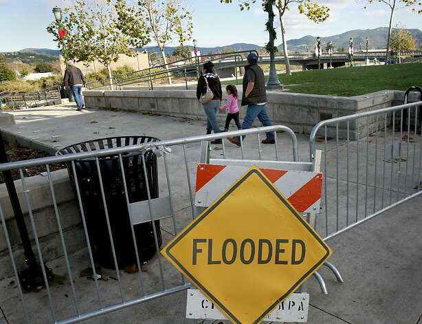 At Veterans Memorial Park, people ignored flood signs and gates to get a view of the rising Napa River under sunny skies. The third of the big storms to hit the Bay Area this weekend dropped a lot of rain but thankfully failed to flood the major rivers including the Napa river Sunday December 2, 2012. Photo: Brant Ward, The Chronicle