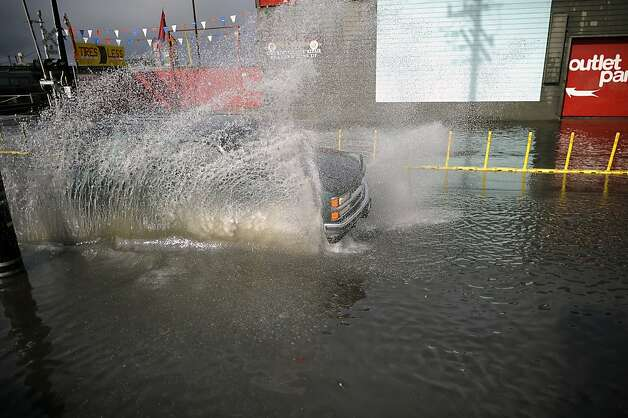 A truck splashes along High St. near the 880 freeway in Oakland, which was partially under water after heavy rains during the morning of Sunday December 2nd, 2012. Photo: Michael Short, Special To The Chronicle