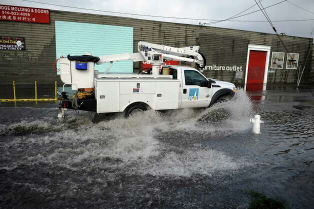 A PG&E truck splashes along High St. near the 880 freeway in Oakland, which was partially under water after heavy rains during the morning of Sunday December 2nd, 2012. Photo: Michael Short, Special To The Chronicle
