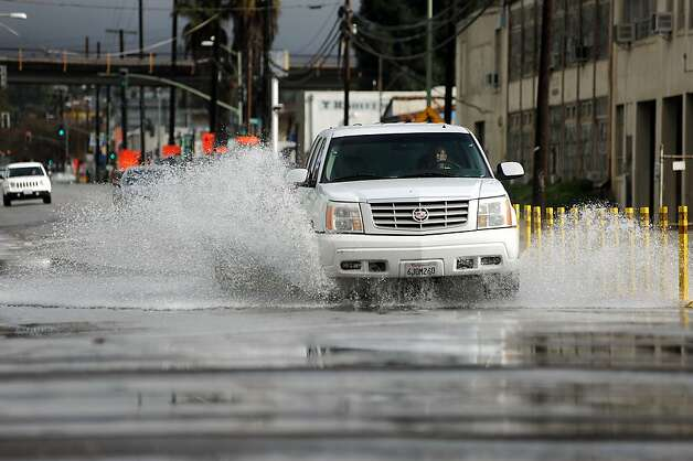 Cars splash along High St. near the 880 freeway in Oakland, which was partially under water after heavy rains during the morning of Sunday December 2nd, 2012. Photo: Michael Short, Special To The Chronicle