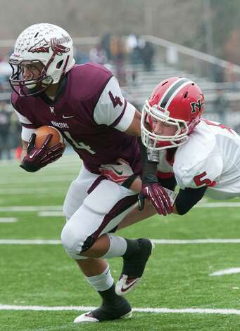 New Canaan high school's Graham Wagner tries to pull down Windsor high school's Terrell Huff in the CIAC class L semifinal football tournament game played at Bunnell high school, Stratford, CT on Sunday December 2nd, 2012. Photo: Mark Conrad / Stamford Advocate Freelance