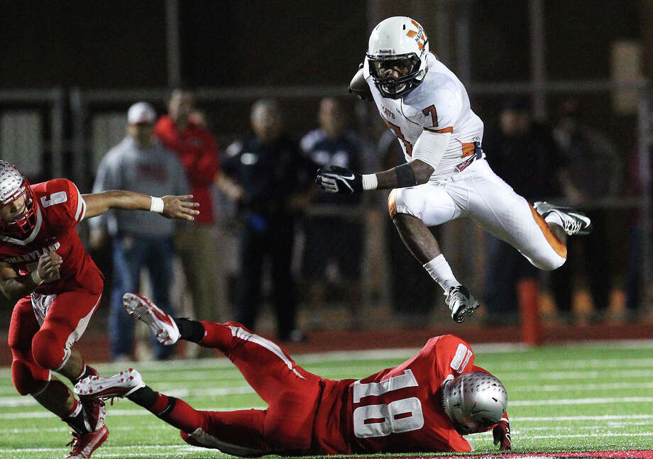 Madison's Marquis Warford (07) leaps over Mission Sharyland's Jon Barraza (18) in the second half in the Class 5A Div. I playoff game in Corpus Christi on Friday, Nov. 30, 2012. Photo: Kin Man Hui, San Antonio Express-News / © 2012 San Antonio Express-News