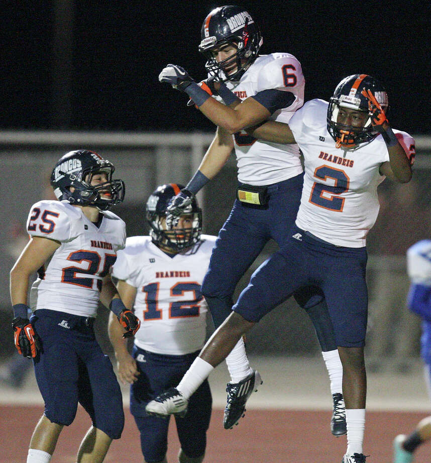 Brandeis' Trevor Hernandez (from left) watches as teammates Brandeis' Alec Sifuentes and Brandeis' Kadarius Lee celebrate after Lee scored a touchdown on a punt return against Del Rio during first half action Friday Nov. 30, 2012 at Eagle Pass ISD Stadium in Eagle Pass, Tx Photo: Edward A. Ornelas, San Antonio Express-News / © 2012 San Antonio Express-News
