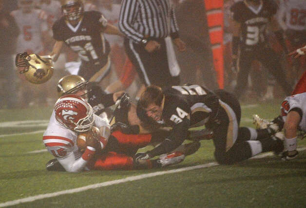 Hand's Matthew Walsh loses his helmet as he tackles Masuk's Malik Cummings in the first half of Hand's 42-23 victory in the Class L state semifinals at West Haven High School on Sunday, December 2, 2012. Photo: Brian A. Pounds / Connecticut Post
