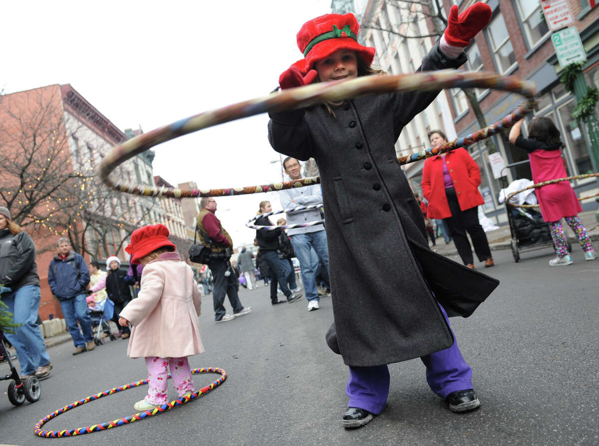 Stella Myers, 5, of Niskayuna masters the hula hoop as her sister Victoria, 1 1/2, left, tries her best during the 30th annual Victorian Stroll Sunday Dec. 2, 2012 in Troy, N.Y. (Lori Van Buren / Times Union)