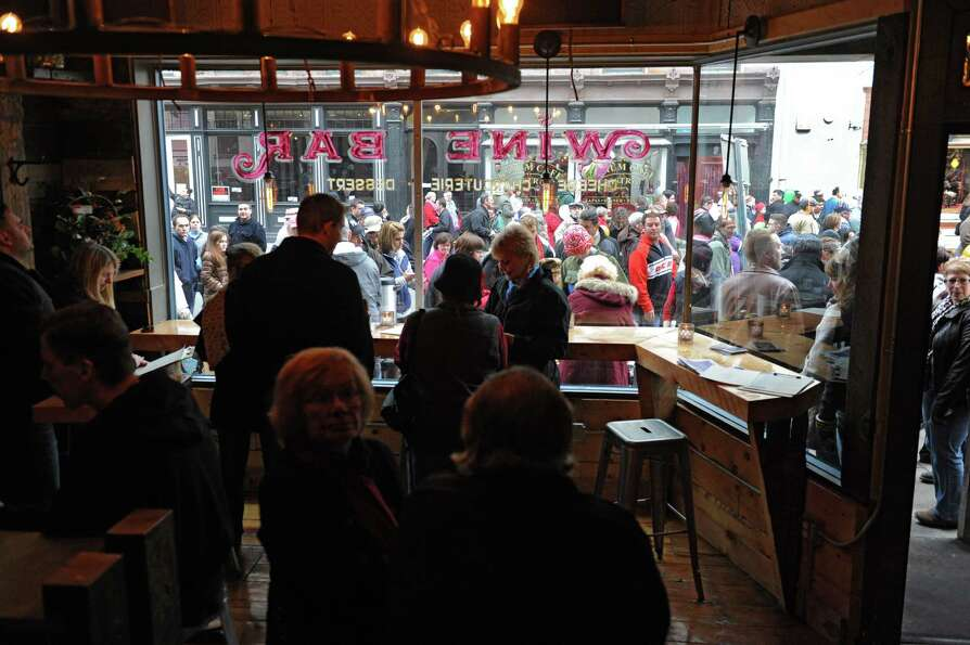 Crowds of people walk by The Charles F. Lucas Confectionery Wine Bar on Second St. during the 30th a