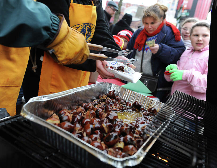 Laura Kotary from Delmar and her daughter Ava-Maye, 9, get some roasted chestnuts sold by members of the Kiwanas Club during the 30th annual Victorian Stroll Sunday Dec. 2, 2012 in Troy, N.Y. (Lori Van Buren / Times Union) Photo: Lori Van Buren