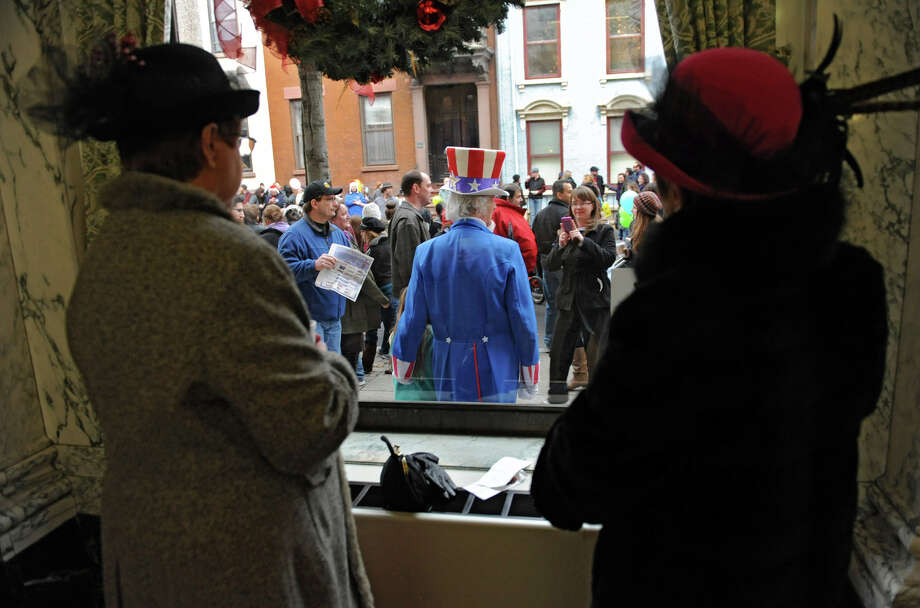 Noreen Iacobucci of Waterford, left, and her sister Jan Sullivan of Clifton Park dressed in victorian costumes watch people take photos of Uncle Sam from a window during the 30th annual Victorian Stroll Sunday Dec. 2, 2012 in Troy, N.Y. (Lori Van Buren / Times Union) Photo: Lori Van Buren