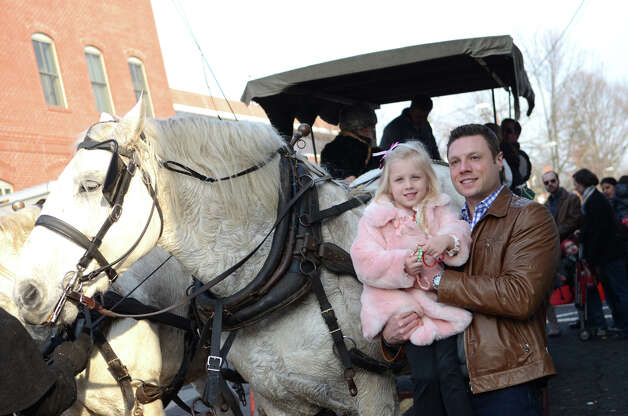 Dr. Christian Whitney and his daughter, Alexa, 4, of Greenwich, pose for a photograph next to a carriage horse during the fourth annual Holiday Stroll Weekend in Greenwich on Sunday, Dec. 2, 2012. Whitney is a doctor at Greenwich Hospital. Photo: Amy Mortensen / Connecticut Post Freelance