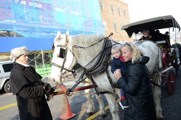 Bryanne Crabb and her son Xander, 2, of Greenwich, greet carriage horses during the fourth annual Holiday Stroll Weekend in Greenwich on Sunday, Dec. 2, 2012. Photo: Amy Mortensen / Connecticut Post Freelance