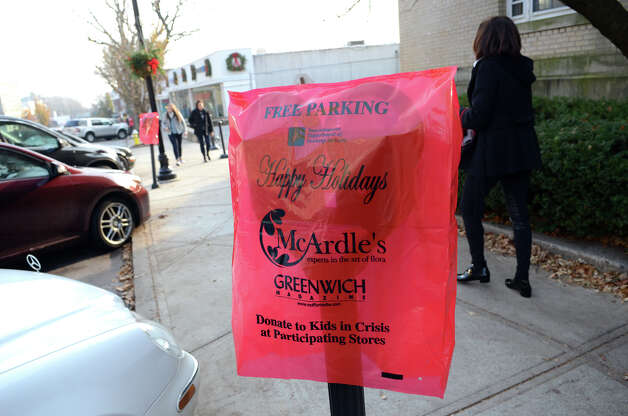 A red free parking sign covers a meter on Greenwich Avenue during the fourth annual Holiday Stroll Weekend on Sunday, Dec. 2, 2012. Photo: Amy Mortensen / Connecticut Post Freelance