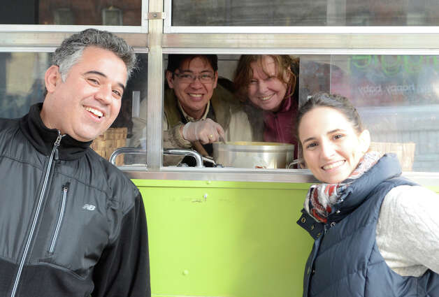 Whole Foods of Greenwich employees Omar Guernah, Enrique Rodriguez, Linda Kyriakos and Ashley Larkin pose for a photo in front of their food truck on Greenwich Avenue during the fourth annual Holiday Stroll Weekend on Sunday, Dec. 2, 2012. Photo: Amy Mortensen / Connecticut Post Freelance