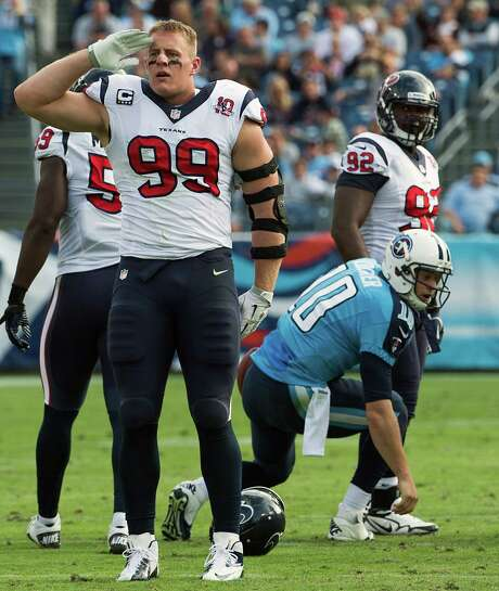 Texans defensive end J.J. Watt lost his helmet during a sack of Jake Locker, but he picked up a distinction unprecedented in NFL history, becoming the first player with 15 sacks and 15 passes broken up in one season. Photo: Smiley N. Pool, Staff / © 2012  Houston Chronicle