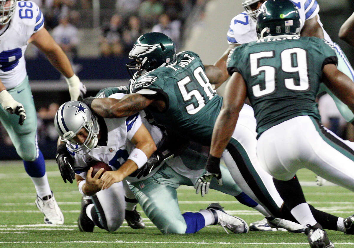 Dallas Cowboys' quarterback Tony Romo is sacked by Philadelphia Eagles' defensive ends Brandon Graham, (54), and Trent Cole, (58), during the first half at Cowboys Stadium in Arlington, Texas, Sunday, Dec. 2, 2012.