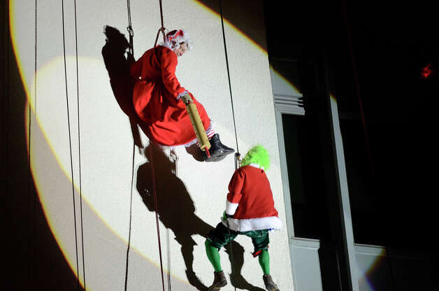 Mrs. Claus fends off the Grinch with a rolling pin as they join Santa, Rudolph, Brian Cashman, Bobby Valentine and friends in a holiday rappelling celebration down the side of the Landmark Building in downtown Stamford, CT on Dec. 2, 2012. Photo: Shelley Cryan / Shelley Cryan for the Stamford Advocate/ freelance Shelley Cryan