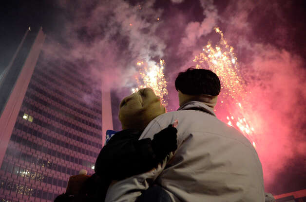 R.K. Javalkar and son Adit, 4 1/2, Stamford, enjoy the fireworks following a holiday rappelling celebration where Santa, Rudolph, Brian Cashman, Bobby Valentine and friends had dropped down the side of the Landmark Building, shown at left, in downtown Stamford, CT on Dec. 2, 2012. Photo: Shelley Cryan / Shelley Cryan for the Stamford Advocate/ freelance Shelley Cryan