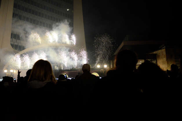 Hundreds enjoy fireworks after a holiday rappelling celebration where Santa, Rudolph, Brian Cashman, Bobby Valentine and friends had dropped down the side of the Landmark Building, shown at left, in downtown Stamford, CT on Dec. 2, 2012. Photo: Shelley Cryan / Shelley Cryan for the Stamford Advocate/ freelance Shelley Cryan