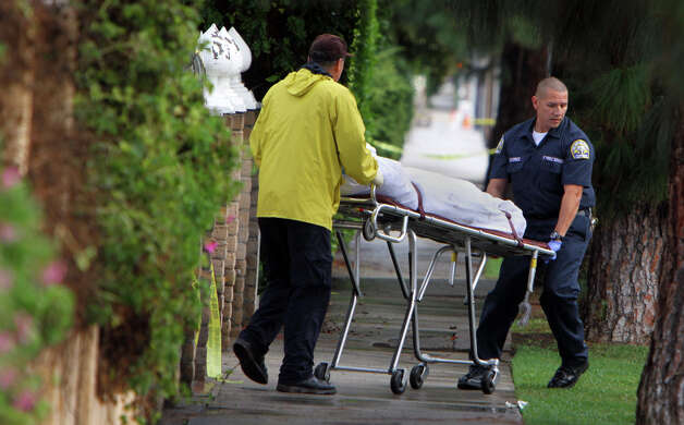 A covered body is removed from the scene on a gurney after police responded to a report of a shooting and found the bodies of four people outside a boarding house in Northridge, Calif., Sunday, Dec. 2, 2012. (AP Photo/Los Angeles Times, Francine Orr) MANDATORY CREDIT  NO MAGS, NO SALES NO FOREIGN NO TELEVISION, INTERNET.  LOS ANGELES DAILY NEWS, ORANGE COUNTY REGISTER, VENTURA COUNTY STAR, INLAND VALLEY DAILY BULLETIN, AND LA OPINION OUT Photo: Francine Orr