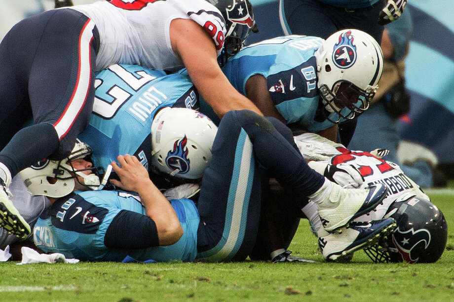 Titans quarterback Jake Locker, bottom, had an afternoon to forget, throwing three interceptions, losing two fumbles and taking six sacks, including this one that resulted in a turnover early in the fourth quarter. Photo: Smiley N. Pool, Staff / © 2012  Houston Chronicle
