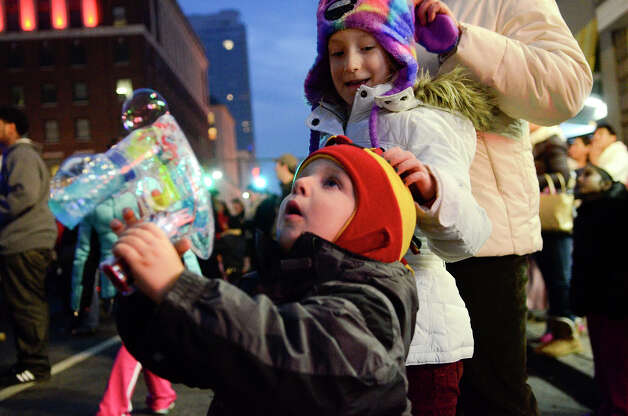 Pawel Cesarczyk, 2 1/2, his cousin Sylwia Lipinski, 7, and Pawel's mother, Gosia Cesarczyk, all Stamford, gather for a holiday rappelling celebration on Broad Street. Moments later, Santa, Rudolph, Brian Cashman, Bobby Valentine and friends would drop down the side of the Landmark Building in a holiday rappelling celebration in downtown Stamford, CT on Dec. 2, 2012. Photo: Shelley Cryan / Shelley Cryan for the Stamford Advocate/ freelance Shelley Cryan