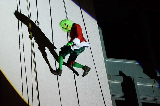 The Grinch joins Santa, Rudolph, Brian Cashman, Bobby Valentine and friends as he drops down the side of the Landmark Building in a holiday rappelling celebration in downtown Stamford, CT on Dec. 2, 2012. Photo: Shelley Cryan / Shelley Cryan for the Stamford Advocate/ freelance Shelley Cryan