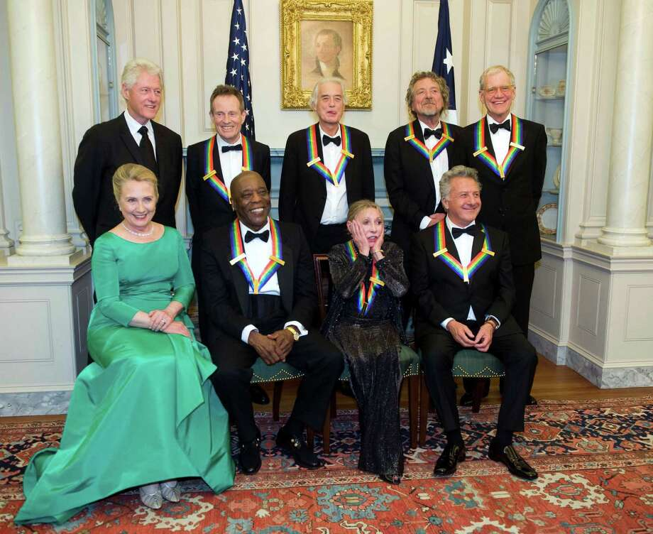 2012 Kennedy Center Honoree Natalia Makarova, front row, second right, reacts to all the photos being taken during a group photo after the State Department Dinner for the Kennedy Center Honors gala Saturday, Dec. 1, 2012 at the State Department in Washington. From left are former President Bill Clinton, Secretary of State Hillary Rodham Clinton, John Paul Johns, Buddy Guy, Jimmy Page, Makarova, Robert Plant, Dustin Hoffman and David Letterman. (AP Photo/Kevin Wolf) Photo: Kevin Wolf