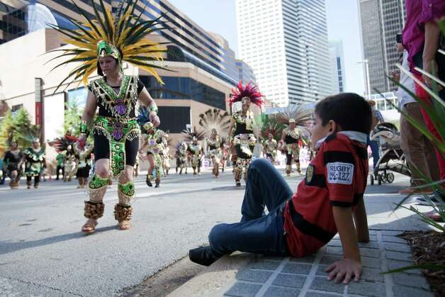 "Robert Rincon, 7, watches as matachines dance and march past Dec. 2, 2012 in Houston. In an expresson of devotion and thanks-giving to  Guadalupe, the Patroness of the Americas, matachines dance and celebrate, and march Dec. 2, 2012 in Houston through the streets of downtown. Now in its 37th year, this is the annual city-wide celebration of the Feast of Our Lady of Guadalupe. The day unites people from across the Archdiocese of Galveston-Houston as thousands come together to rejoice. The event began at noon with a procession from 1700 San Jacinto to the George R. Brown Convention Center. Matachines are indigenous folk dance troupes, mariachis and other singers. The matachines wear elaborate headpieces and traditional Aztec-style dress.  From a press release: ""This celebration in the Hispanic Catholic community means being able to maintain a cultural heritage that derives almost 5 centuries,"" said Gilberto Heredia, president of the Guadalupana Association.  The general community is invited to this annual event.  The event is sponsored by the Guadalupana Association of the Archdiocese of Galveston-Houston. It commemorates the official Church feast day of Our Lady of Guadalupe on December 12. On a hill near a rural village just outside of Mexico City, the Virgin Mary, Our Lady of Guadalupe, appeared to a humble peasant named Juan Diego, now St. Juan Diego. Surrounded by light and speaking in his indigenous tongue of Nahuatl, Our Lady told Juan Diego she wanted a church built to manifest her Son's love and hear the petitions of the faithful. To help him in his mission, she gave him a sign, imprinting her beautiful image on his cloak. From it would flow miracles. The news spread quickly throughout Mexico, and in the following years, millions would convert to Catholicism. The Archdiocese of Galveston-Houston serves 1.2 million Catholics in 10 counties. It is the largest Roman Catholic diocese in Texas and the 12th largest in the United States. Photo: Eric Kayne / © 2012 Eric Kayne"