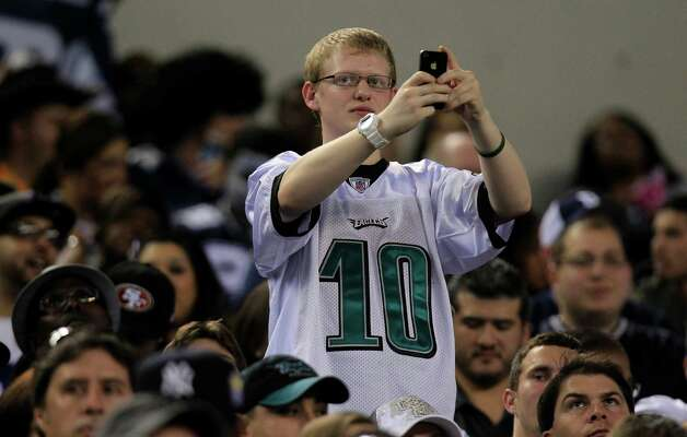 A Philadelphia Eagles fan takes a cell phone pic before before the NFL football game between the Philadelphia Eagles and Dallas Cowboys Sunday, Dec. 2, 2012 in Arlington, Texas. (AP Photo/LM Otero) Photo: LM Otero, Associated Press / AP