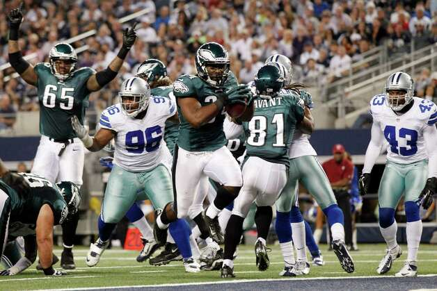Philadelphia Eagles running back Bryce Brown (34) scores a touchdown as tackle King Dunlap (65) celebrates and Dallas Cowboys defensive end Marcus Spears (96) and safety Gerald Sensabaugh (43) react during the first half of an NFL football game, Sunday, Dec. 2, 2012, in Arlington, Texas. (AP Photo/Tony Gutierrez) Photo: Tony Gutierrez, Associated Press / AP