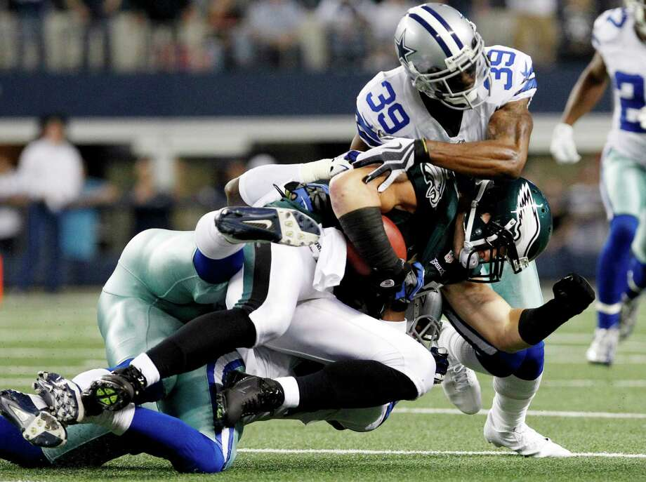 Philadelphia Eagles tight end Brent Celek (87) is brought down by Dallas Cowboys cornerback Brandon Carr (39) and inside linebacker Ernie Sims during the first half of an NFL football game, Sunday, Dec. 2, 2012, in Arlington, Texas. (AP Photo/LM Otero) Photo: LM Otero, Associated Press / AP
