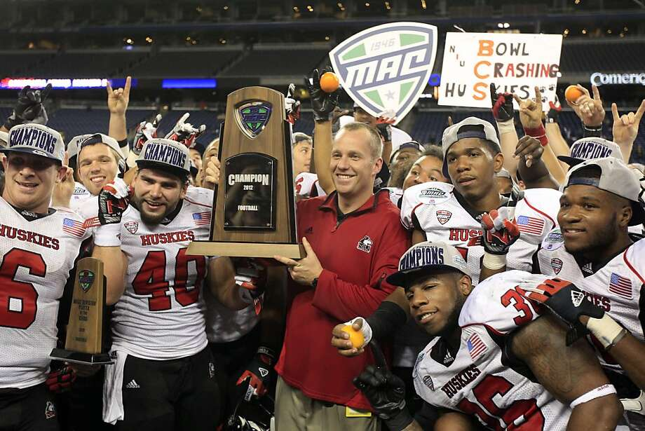 Northern Illinois coach Dave Doeren holds the MAC trophy Friday. By Saturday, he had left for the N.C. State job. Photo: Carlos Osorio, Associated Press