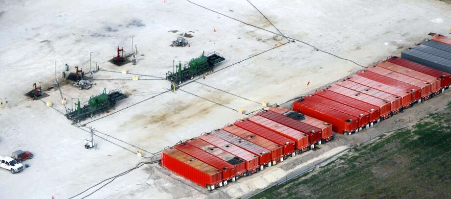 Three well heads, upper left, in Eagle Ford shale oil play are seen in this Friday Nov. 23, 2012 aerial photo near Kenedy. Red so-called frac tanks are positioned at the right edge of the pad site. The containers can each hold 500 barrels of fluid which can be material being prepared to go down the well or material that has come out of the well. (San Antonio Express-News)