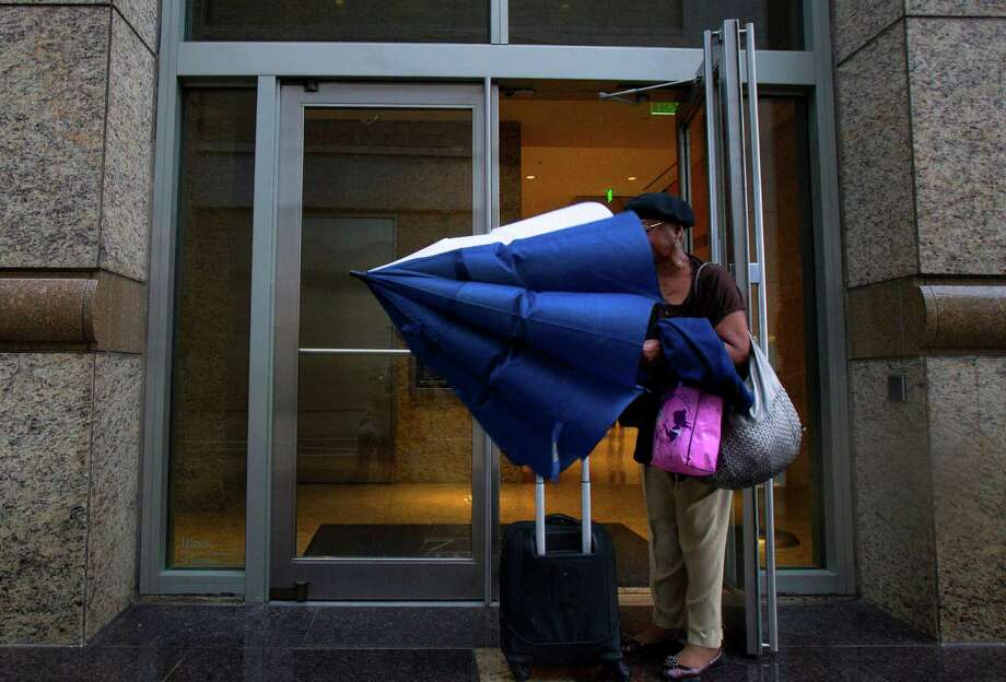 Vivian Brown puts her umbrella away before entering work at TransCanada Monday, Dec. 3, 2012, in Houston. Photo: Cody Duty, Houston Chronicle / © 2012 Houston Chronicle