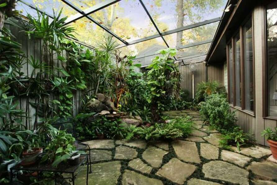 Mossy grass grows through the stone pavers in this secluded, greenhouse-like nook.