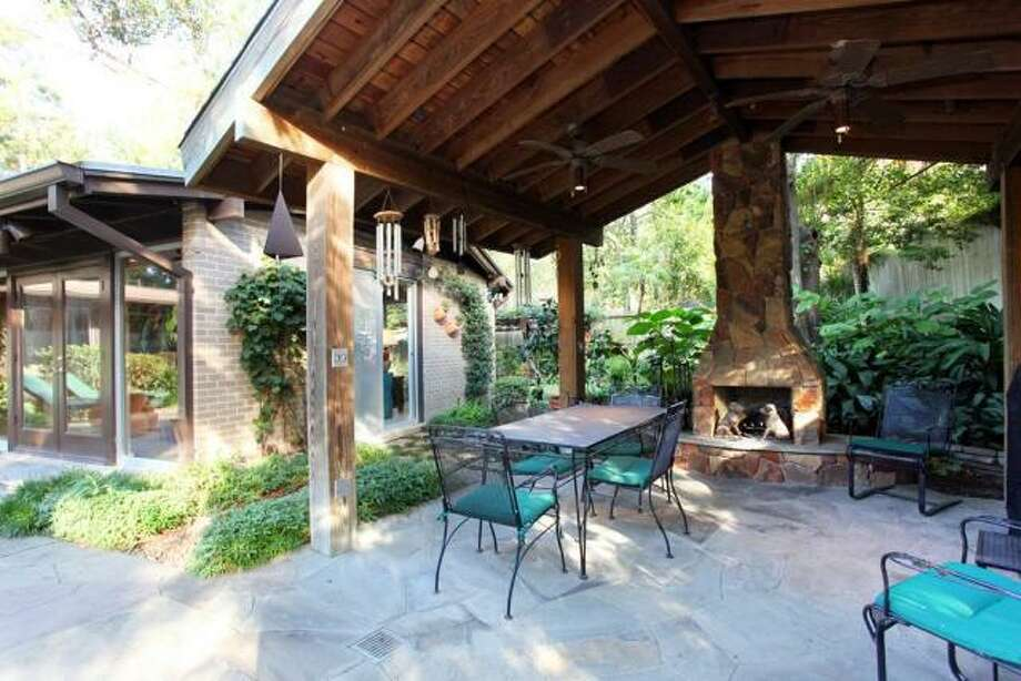 Under the wood pergola is a stone fireplace and sitting area. Photo: John Daugherty Realtors