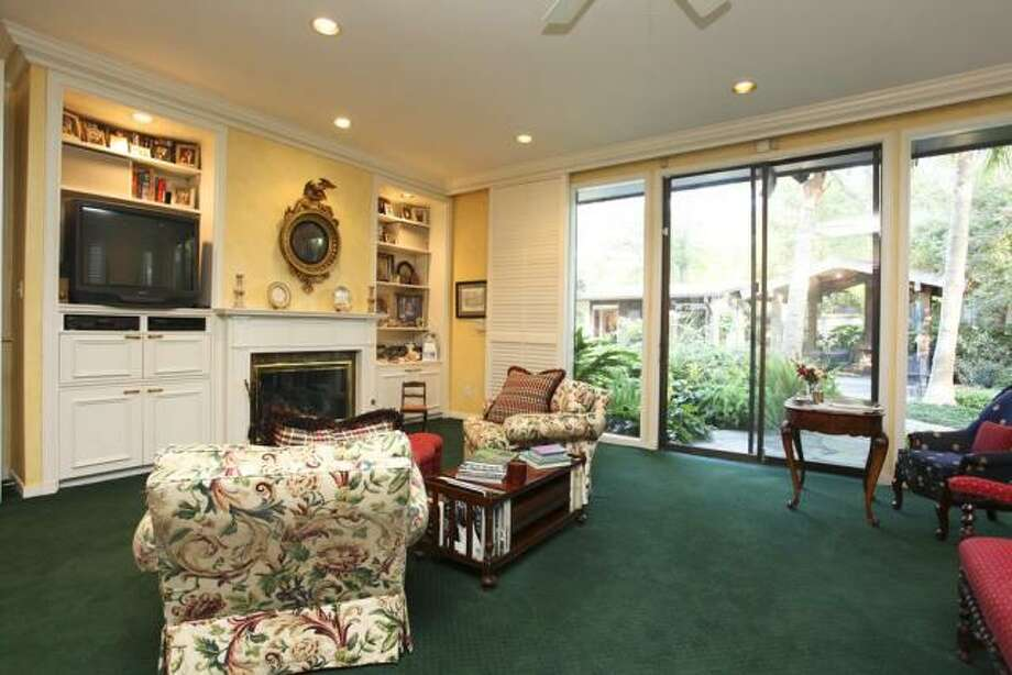 A sitting area in the master bedroom has a fireplace and built-in shelving. Photo: John Daugherty Realtors