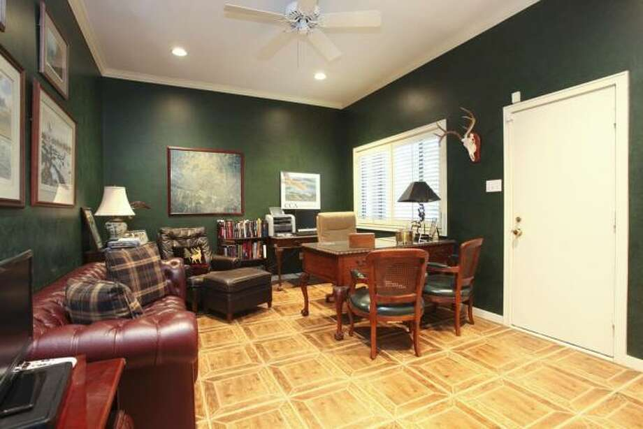 The dark walls and custom wood flooring of the office give the room a stately feel. Photo: John Daugherty Realtors