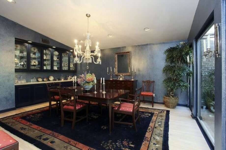 The dining room has a hanging chandelier and a row of glass-fronted cabinets. Photo: John Daugherty Realtors