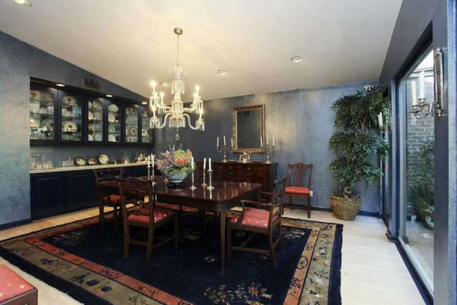 The dining room has a hanging chandelier and a row of glass-fronted cabinets.
