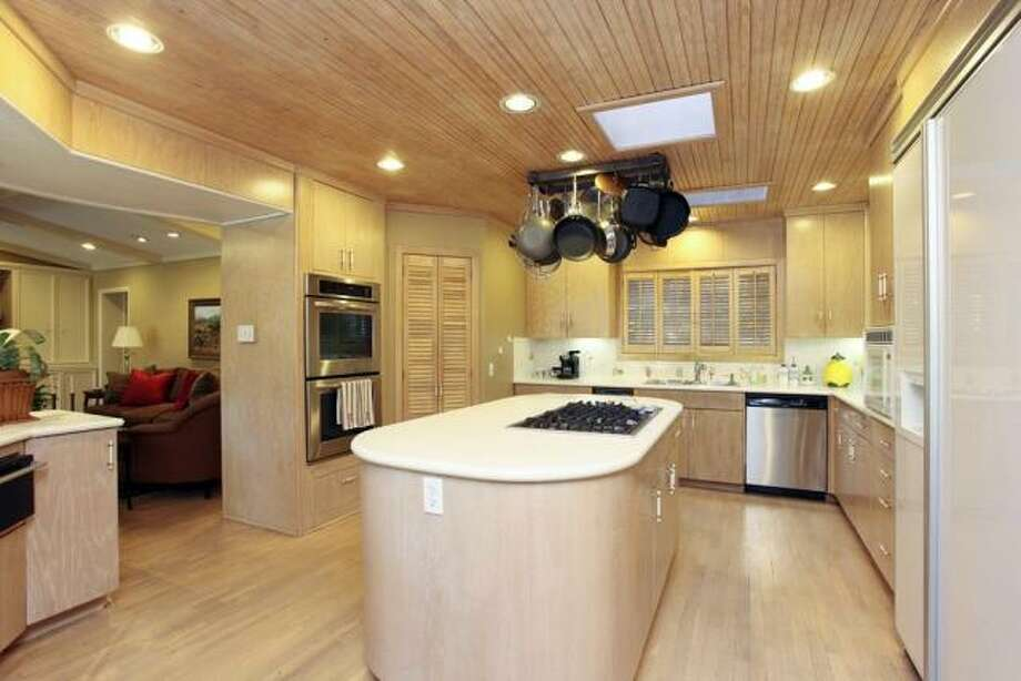 The kitchen is bathed in light wood tones and has recessed lighting, a center island with a range and several stainless steel appliances, including a dishwasher and a double oven. Photo: John Daugherty Realtors