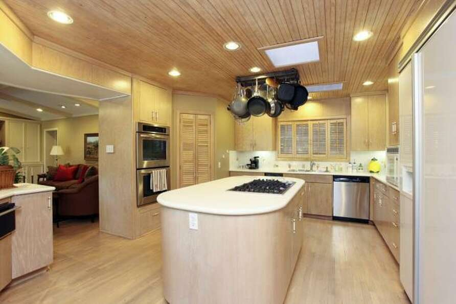 The kitchen is bathed in light wood tones and has recessed lighting, a center island with a range an
