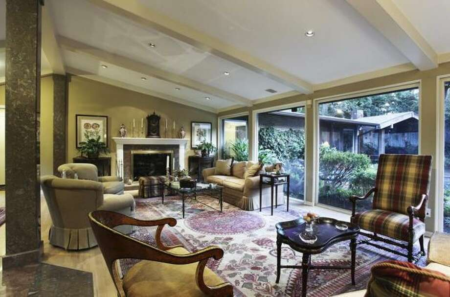 The living room has ample space to accommodate a variety of seating arrangements and overlooks the gardens. Photo: John Daugherty Realtors