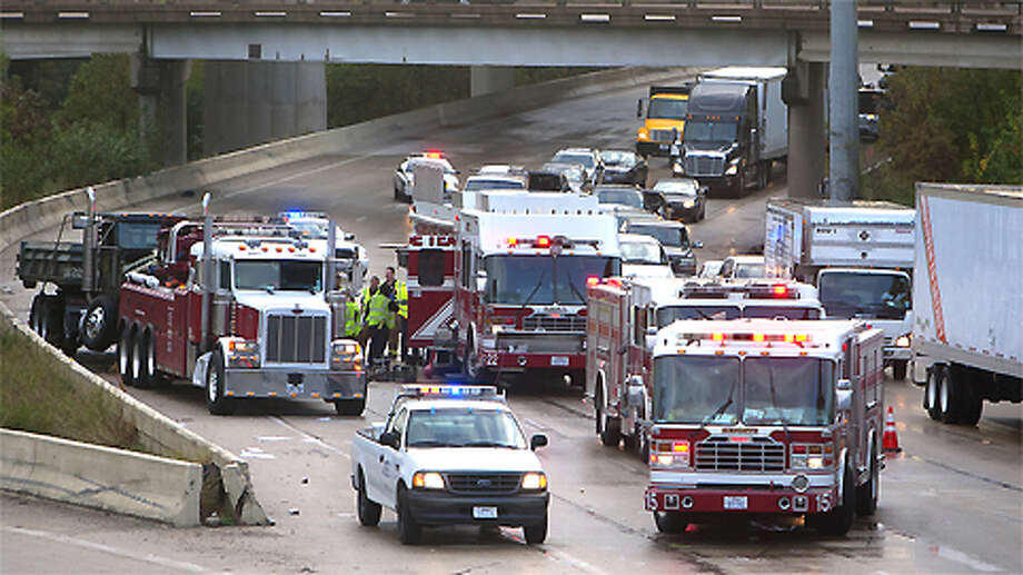 Crews work to clean up a wreck in the West-bound lane of I-10 on the East side of Houston Street, Monday, Dec. 3, 2012, in Houston. All westbound main lanes of Interstate 10 near downtown were blocked after two trucks collided and at least one of them lost its load early today. The 5 a.m. wreck has the interstate backed up for miles from the Taylor exit. Photo: Cody Duty, . / © 2012 Houston Chronicle