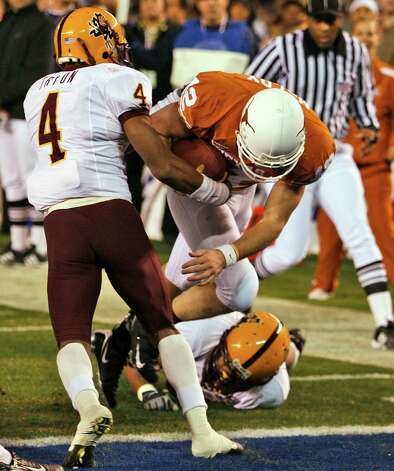 Texas quarterback Colt McCoy plunges into the end zone on a 9-yard touchdown run in the second quarter of the Holiday Bowl football game Thursday, Dec. 27, 2007, in San Diego. At left is Arizona State cornerback Justin Tryon. Photo: Denis Poroy, AP / AP