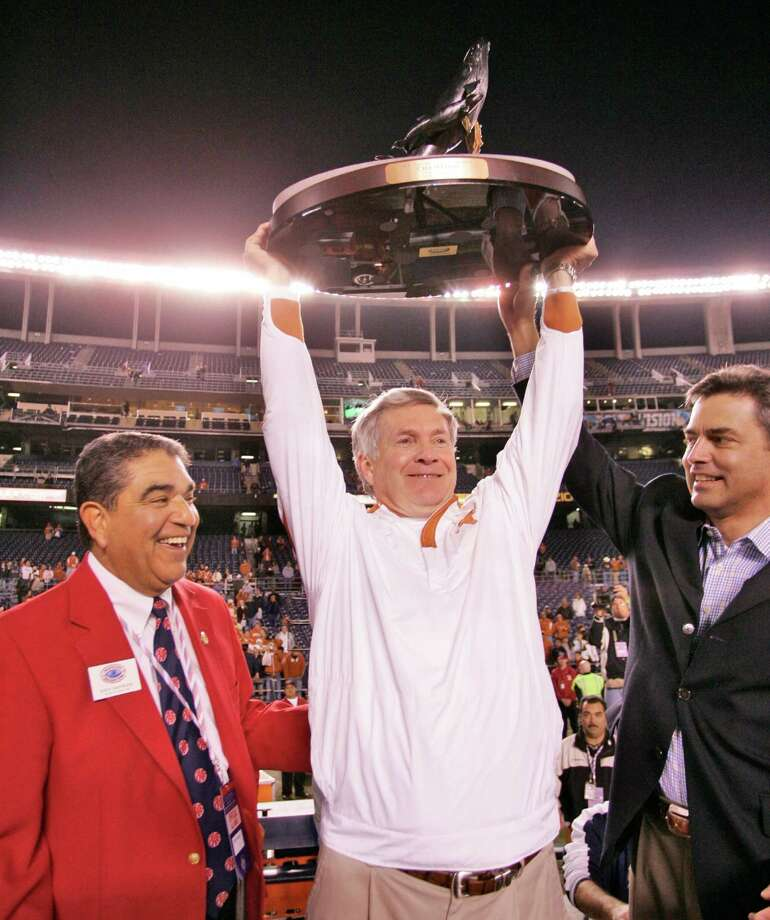 Texas' coach Mack Brown holds the Holiday Bowl trophy after his team defeated Arizona State 52-34 in the 30th Holiday Bowl football game on Thursday Dec. 27, 2007 in San Diego. With coach Brown are Holiday Bowl president Rudy Castruita, left, and Pacific Life CEO Jim Morris. Photo: Chris Park, AP / AP