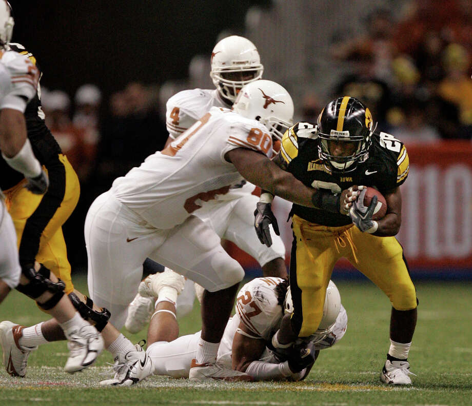 Texas defender Tim Crowder (80) and Michael Griffin stop Iowa running back Damian Sims during fourth-quarter Alamo Bowl action in San Antonio on Saturday, Dec. 30, 2006. WILLIAM LUTHER / STAFF