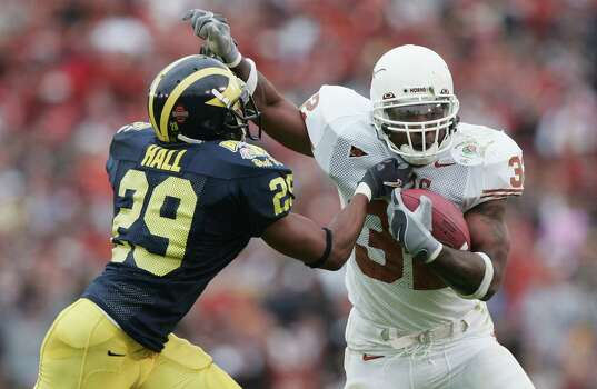 PASADENA, CA - JANUARY 01: Runningback Cedric Benson #32 of the Texas Longhorns avoids a tackle from Leon Hall #29 of the Michigan Wolverines in the 91st Rose Bowl Game at the Rose Bowl on January 1, 2005 in Pasadena, California. Photo: Jed Jacobsohn, Getty Images / 2005 Getty Images