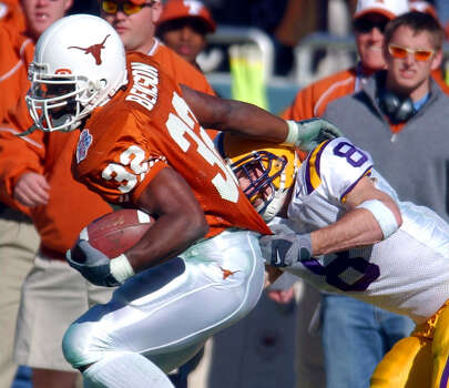 Texas' Cedric Benson (32) tries to shake the tackle of LSU's Jack Hunt (8) Jan. 1, 2003 during the SBC Cotton Bowl Classic in Dallas, Texas. Texas went on to defeat LSU by a score of 35 -20. PHOTO BY EDWARD A. ORNELAS/STAFF Photo: EDWARD A. ORNELAS, SAN ANTONIO EXPRESS-NEWS / SAN ANTONIO EXPRESS-NEWS